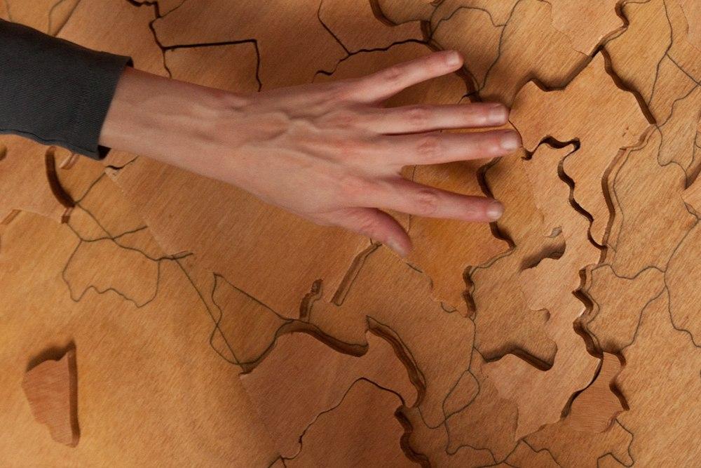 Cartographie Personnelle, détail, sculpture en forme de puzzle interactif, dessin en crayon noir, bois, contre-plaqué, vernis, 120 cm x 83 cm x 2 cm, 2012