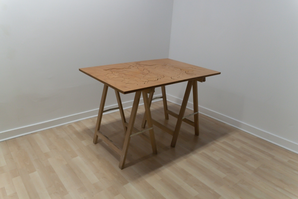 Personal Cartography, interactive wooden puzzle game. Black pencil drawing on varnished plywood. Sculpture dimensions 120 cm x 83 cm x 2 cm thick. Shown on pine sawhorse table legs with outline element hung on the wall. 2012.