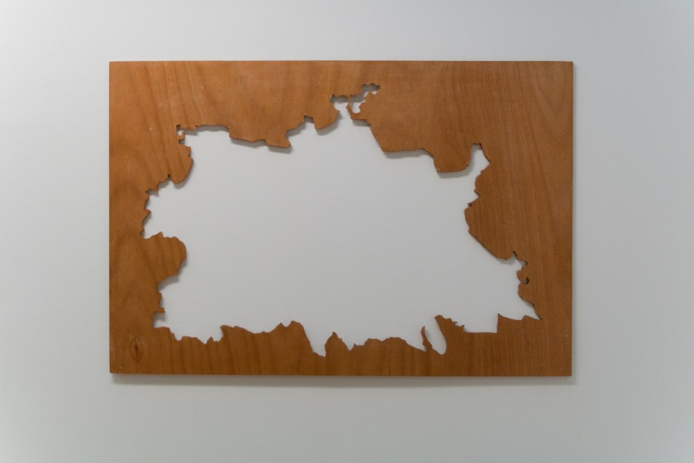 Personal Cartography, interactive wooden puzzle game. Black pencil drawing on varnished plywood. Sculpture dimensions 120 cm x 83 cm x 2 cm thick. Shown on pine sawhorse table legs with outline element hung on the wall. 2012. Detail.